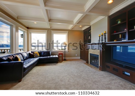 Large luxury living room with TV, water view, and shelves. - stock photo