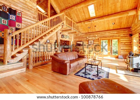 Large luxury log cabin house living room with large staircase. - stock photo