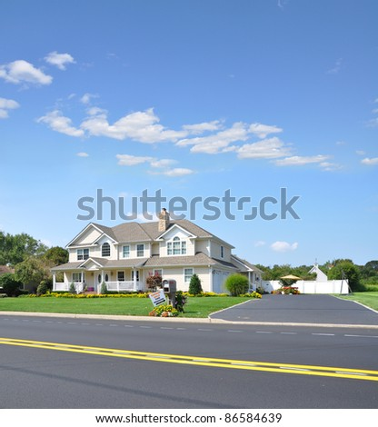 Large Luxury Two Car Garage Suburban McMansion style Home in Residential Neighborhood with Garage Sale Sign next to Mailbox on Sunny Blue Sky Day - stock photo