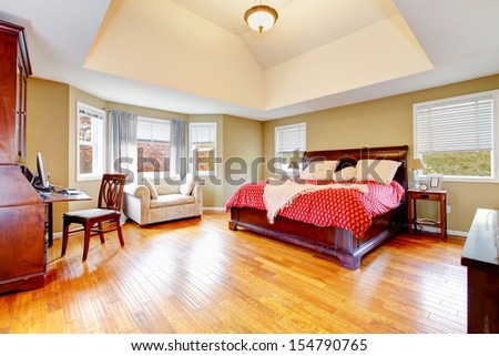Large master bedroom interiors with vaulted ceiling and hardwood floors.