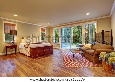 Large master bedroom with hardwood floor and sliding glass door to backyard. - stock photo