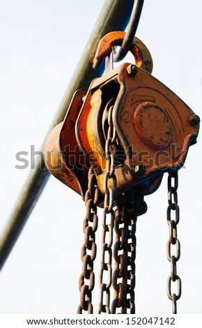 Large metal hook and chains attached to a pulley - stock photo