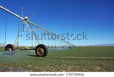 Large, mobile sprayer irrigates the fields with a low evaporation watering system - stock photo