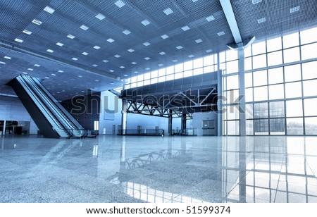 Large modern hall with windows and escalator - stock photo