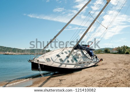 Large modern sailing yacht stranded on a beach after storms in the Mediterranean - stock photo