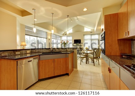 Large modern wood kitchen with living room and high ceiling and ivory walls. - stock photo