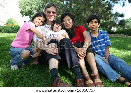 Large multiracial family sitting on lawn - stock photo