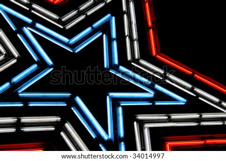 Large neon lit star with patriotic colors of red, white and blue.  Shot against the night sky. - stock photo