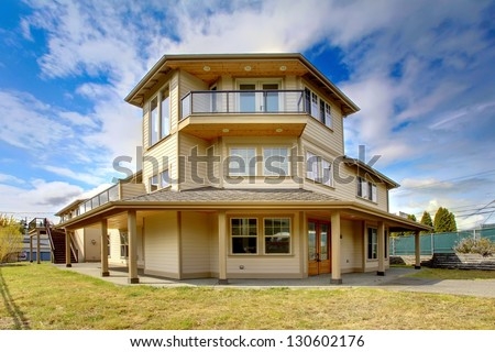Large New luxury home exterior with balconies, three floors. - stock photo