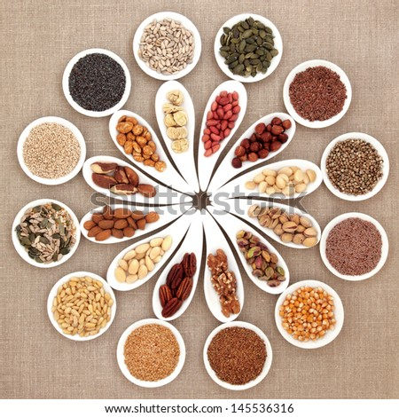 Large nut and seed food selection in porcelain bowls over hessian background. - stock photo