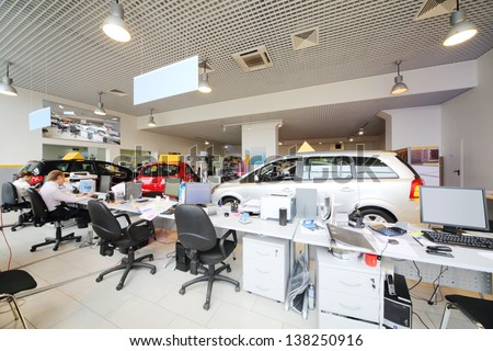 Large office of shop selling cars. Office workers sit at computers. - stock photo