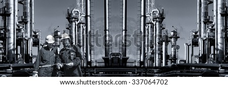 large oil and gas refinery, panoramic view with two oil-workers in foreground - stock photo