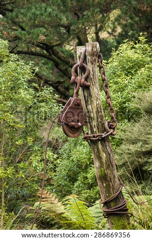 Large old steel pulley with a bug steel chain on a post. - stock photo