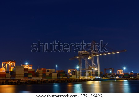 Large operating crane at harbor night time