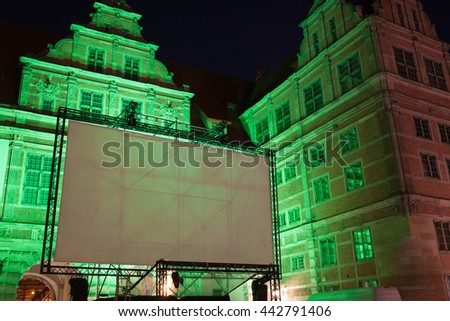 Large outdoor movie projector screen, empty display ready for projection at night, illuminated Green Gate, Old Town of Gdansk, Poland