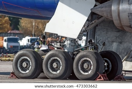 Large passenger airplane maintenance personnel working on aircraft main landing gear repair detail exterior close up view