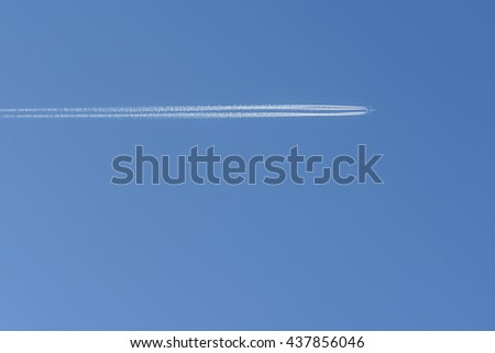 large passenger plane and contrail on blue sky - stock photo