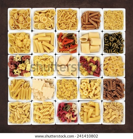 Large pasta dried food sampler in square dishes over brown lokta paper background. - stock photo