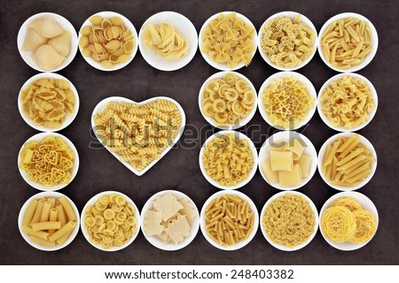 Large pasta food selection in round bowls and in a heart shaped bowl over brown background. - stock photo