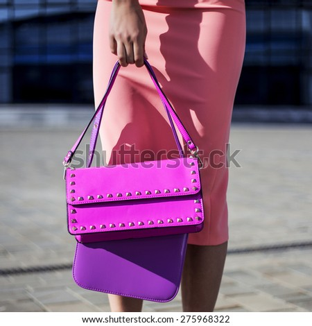 Large pictures of feet and bright beautiful girl beautiful shoe holding bags in their hands. - stock photo