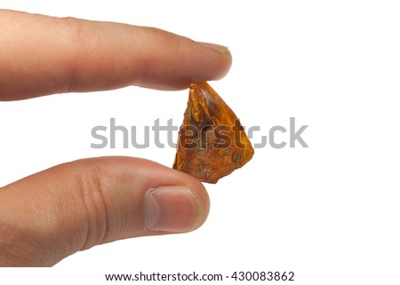 large piece of amber, between fingers on white background