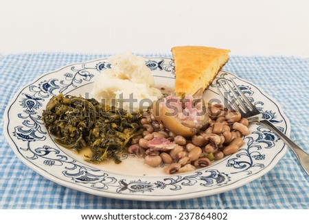 Large piece of fat ham hock in black-eyed peas with collard greens and mashed potatoes and slab of cornbread. - stock photo