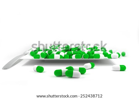 large pile of green colored pills on white plate silver spoon - stock photo