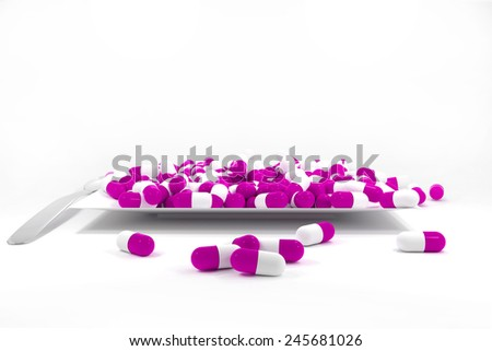 large pile of purple colored pills on white plate silver spoon - stock photo