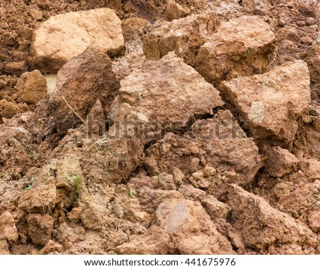 Large piles of clay, which dropped to the bottom and break apart because of water erosion. - stock photo