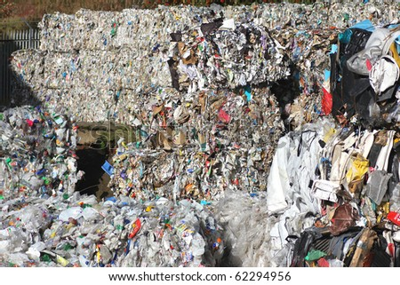 Large piles of recycling waste in recycling centre - stock photo