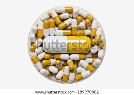 Large pill surrounded by smaller pills in a petri dish - stock photo