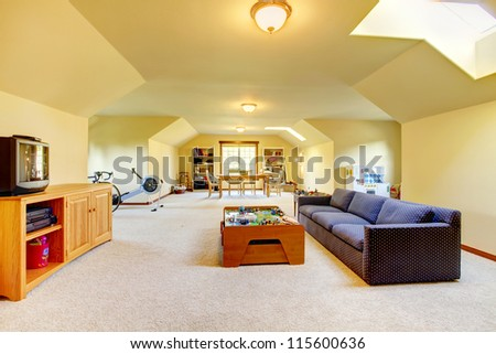 Large play room with Tv, sport and games. Home interior, yellow walls and beige carpet. Very long bright room. - stock photo