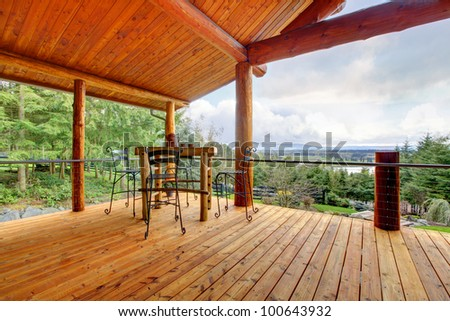 Large Porch of the log cabin with small table and forest view. - stock photo
