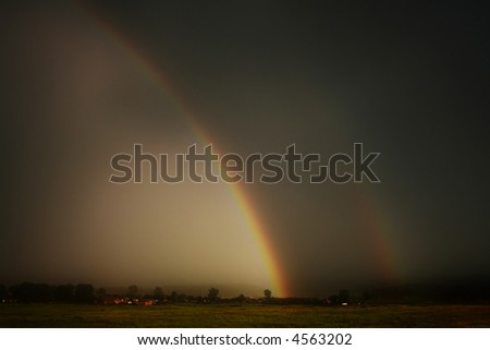 Large rainbow during thunderstorm over farmers field - stock photo