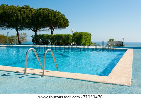 Large rectangular swimming pool against the background of the ocean - stock photo