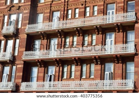 Large red bricked hotel with white balcony