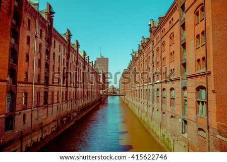 Large river canal with bricks buildings on the sides, sun and shadow, color mix