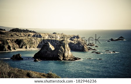 Large rocks jutting out of the ocean along the California coastline.