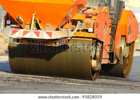 Large rolling machinery paving a road - stock photo