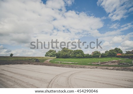 Large rural yard with tracks in sand and green fields