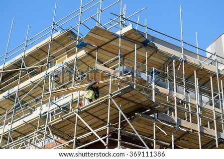 Large scaffolding on a building with worker holding wooden board
