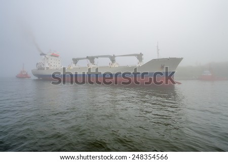 Large ship in the fog enters a port, Gdansk, Poland - stock photo