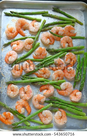 Large shrimp on a sheet pan with asparagus, black pepper and coarse salt