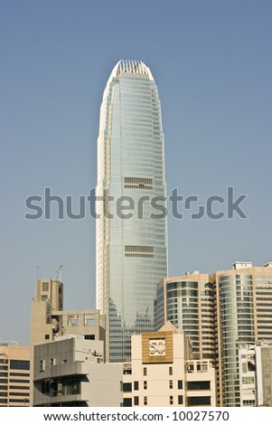 Large skyscraper in Hong Kong, surrounded by smaller buildings. - stock photo