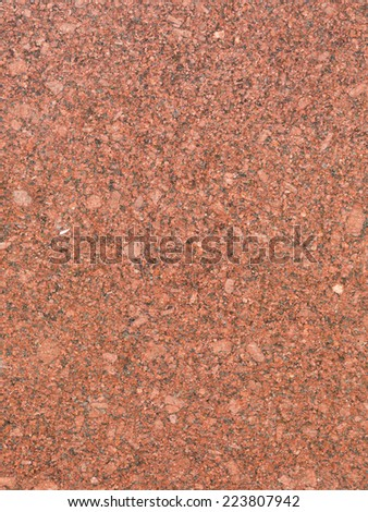 large smooth solid red granite slab with light splashes - stock photo