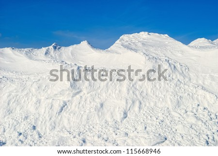 Large Snow Drift Against Blue Sky - stock photo