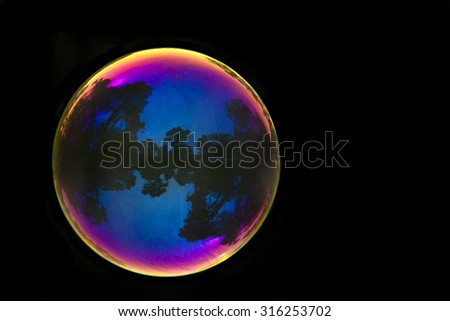 Large soap bubble reflecting outdoor park scene from San Francisco Golden Gate Park isolated on dark background - stock photo