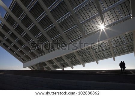 Large solar panel in Barcelona Forum recreation park. Couple looking at the horizon. - stock photo