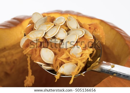 Large spoon of pumpkin seeds scraped from inside pumpkin to prepare for carving jack o lantern