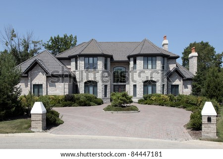 Large stone home with pillars and brick driveway - stock photo